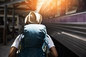 Young Asian Traveler With Backpack In The Railway, Backpack And Hat At The Train Station With A Trav poster