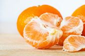 Close Up Of Whole, Peeled And Segmented Satsumas, On A Light Wood Scratched Old Chopping Board With  poster