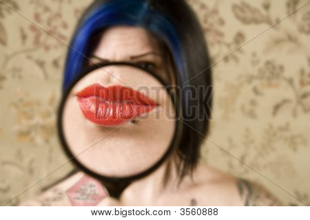 Pretty Woman With A Magnifying Glass In Front Of Her Mouth