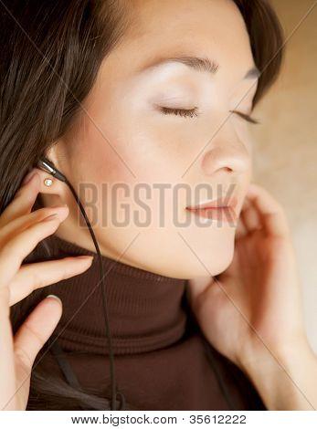 Beautiful asian woman listening music in headphones