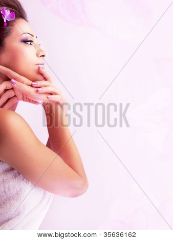 Pretty woman enjoying dayspa, beautiful female with purple flower in brown hair isolated on white background, side view of cute girl face, sexy young lady relaxing in spa salon, beauty care concept