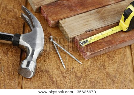 Hammer, nails, tape measure and pieces of wood