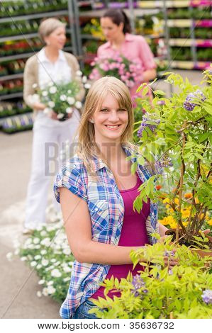 Smiling woman at garden center shopping for house plants