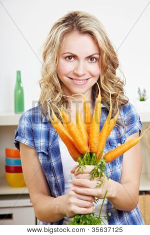Smiling happy woman in her kitchen with bunch of carrots