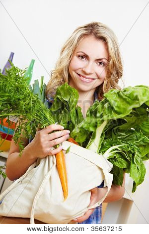 Smiling young woman in kitchen with shopping bag full of vegetables