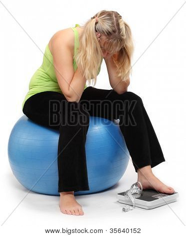 Depressed overweight woman on a weighing machine.