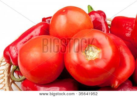 Few tomatoes and red pepper in the punnet, on the white background