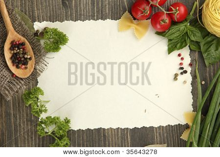 paper for recipes vegetables, and spices on wooden table