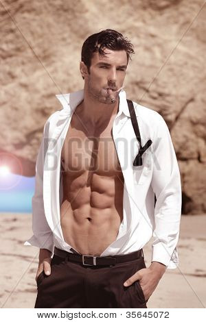 Sexy handsome playboy outdoors with shirt open revealing hot body and nice abs
