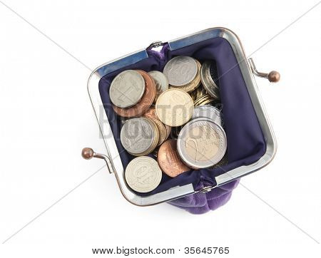 Gold, bronze and silver coins are in a violet purse, isolated on white. A great number of coins symbolize wealth, richness, income and profit. Close up shot.