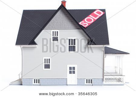 Real estate concept - home architectural model with Sold sign, isolated