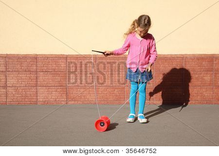 Beautiful little girl plays with yo-yo on sunny day outdoor.