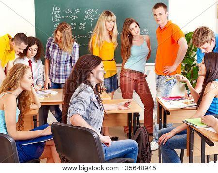 Group happy student near blackboard in classroom.
