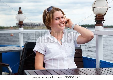Beautiful Caucasian Young Woman In White Shirt Calling With Mobile Phone At Cafe Table.