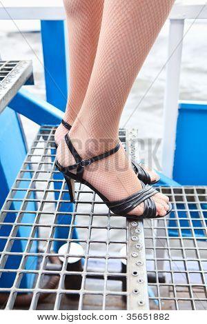 weibliche Schönheit Beine in Fischnetz-Strumpfhose und Schuhe in Stöckelschuhen stehen auf Treppen