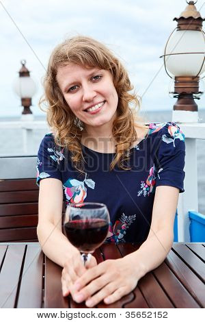 Pretty Woman In Dress With Wine Glass Sitting At The Table