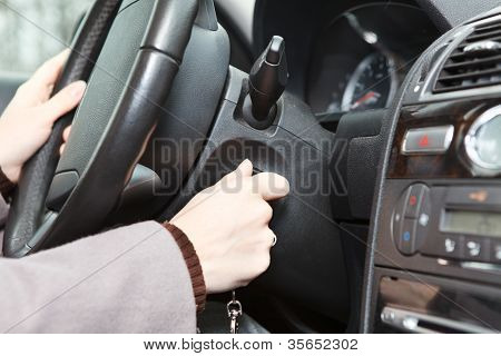 Female Hand Starting A Car Engine With Ignition Key