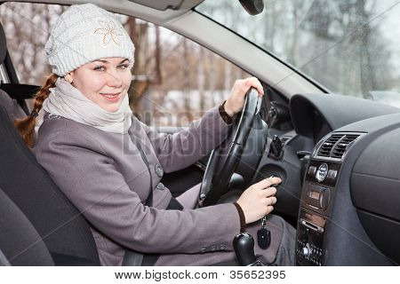 Female Driver Putting Ignition Key And Starting Car