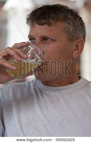 älterer Mann trinkt Bier aus dem Glas eine enge bis