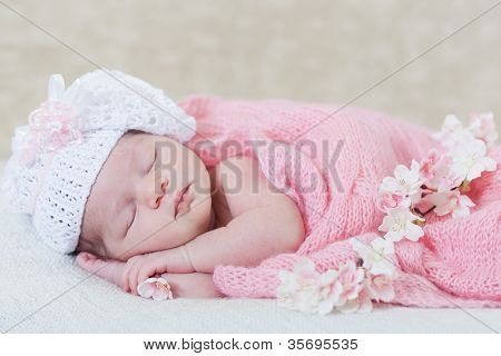 newborn girl sleeps with spring flowers