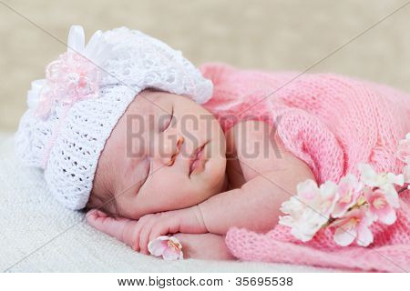 newborn girl sleeps with spring flowers