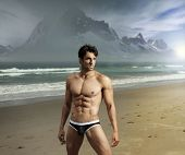 stock photo of tease  - Muscular fit sexy guy on remote scenic beach location with dramatic mountains in background - JPG