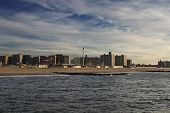 stock photo of heatwave  - Coney Island beach at sunrise with building in the background and ocean in the foreground - JPG