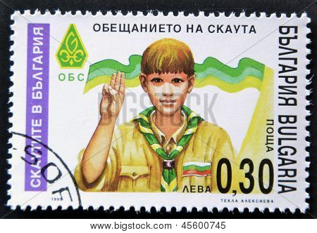 A stamp printed in Bulgaria shows a boy Scout Giving scout sign