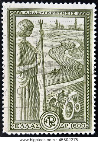 A stamp printed in Greece shows statue of Ceres overlooking an agricultural field