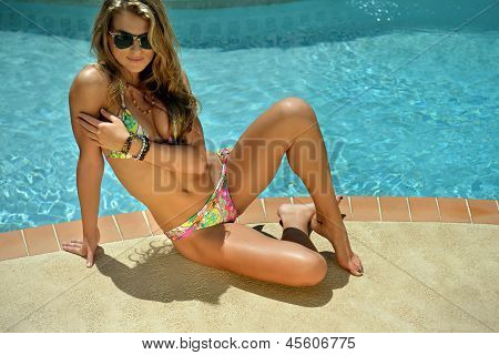 Bikini model sitting in front of pool outside