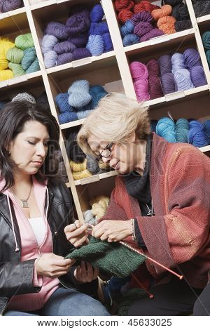 Woman knitting in front of yarn