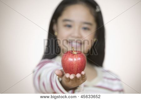 Portrait of young girl holding apple