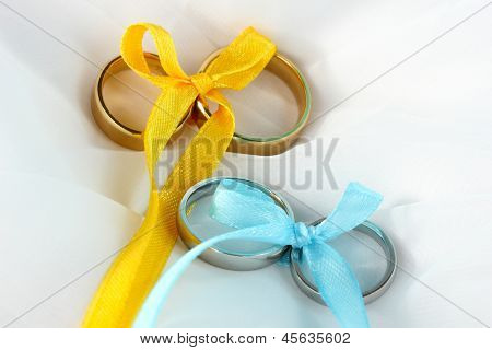 Wedding rings tied with ribbon on cloth background