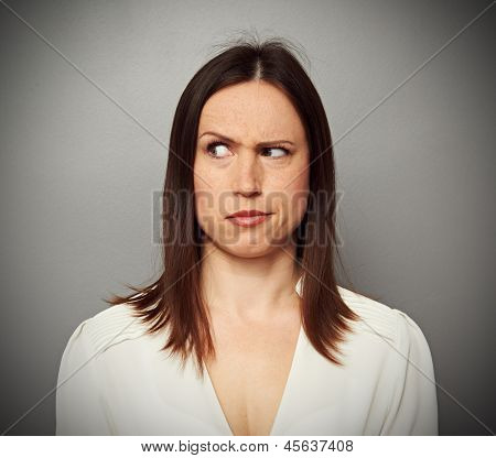 young brunette looking with misunderstand. studio portrait over grey background