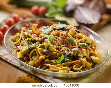 pasta with eggplants zucchinis tomatoes and curry, selective focus