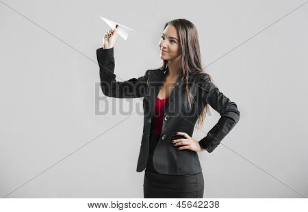 Beautiful business woman throwing a paper plane, over a gray background