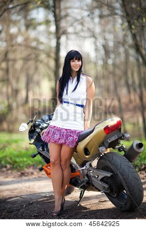 girl is standing next to a motorcycle