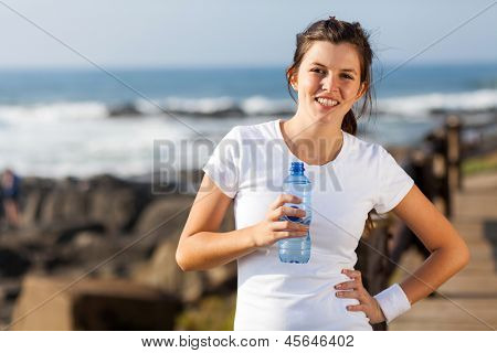 cute teen girl drinking water after morning workout at the beach