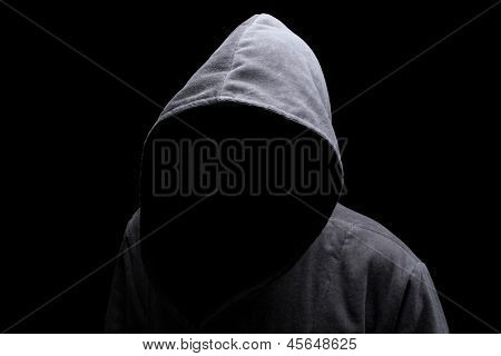 Menacing silhouette of hooded man in the shadow