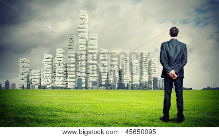 Successful young businessman standing against modern cityscape