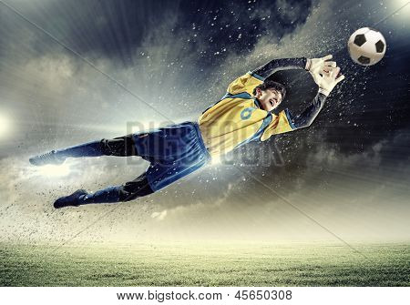 Goalkeeper catches the ball . At the stadium, in the spotlight.