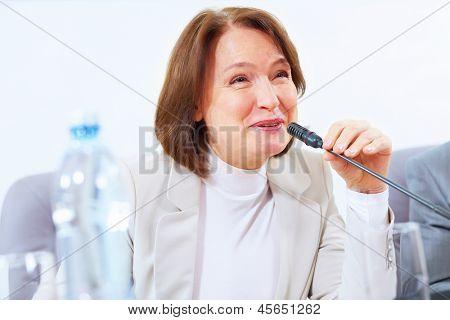 Image of businesswoman at business meeting speakig in microphone