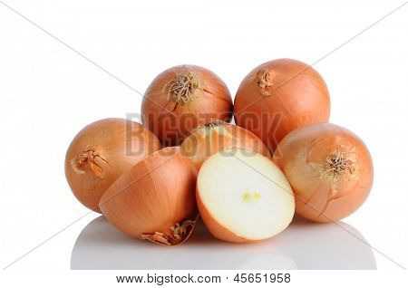 Closeup of a pile of yellow onions on a white surface with reflection. One onion is cut in half, horizontal format.