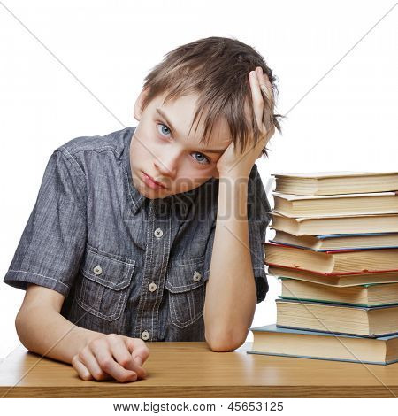 Portrait of upset schoolboy sitting at desk with books holding his head