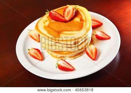A picture of american style pancakes served with stawberries