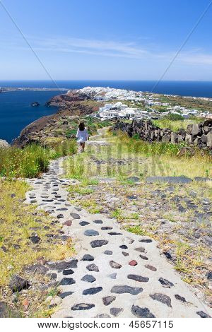 A woman walks along a path in Santorini