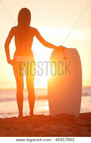 Surfer beach woman with water sport bodyboard. Surf girl enjoying sunset view and summer sunshine after bodyboarding on travel vacation holidays. Fit Asian bikini model living healthy lifestyle