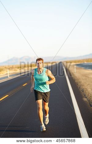Male runner jogging and running on road in nature landscape. Fit fitness model man working out living healthy lifestyle training for marathon. Young caucasian model in his twenties.