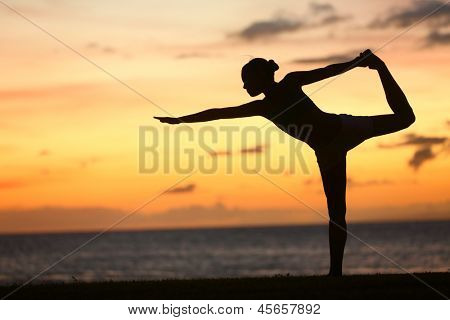Yoga woman in serene sunset at beach doing king dancer pose. Meditation and balance exercise at sunrise or sunset with female yoga instructor exercising outside in nature.