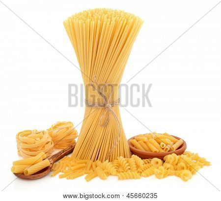 Pasta varieties of spaghetti tied in a bundle, tagliatelle, penne, macaroni, fusilli, rigatoni and fiorelli over white background.